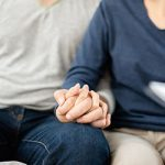 Young man and woman planning with professional consultant. Couple sitting on sofa and holding hands together.