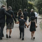 Grieving family walking through a cemetery
